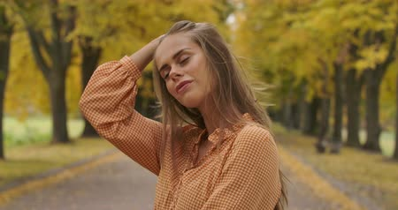 crows feet : Profile portrait of a confident Caucasian woman standing on the road in the autumn park. Charming girl in mustard dress tucking hair behind ear and smiling. Cinema 4k footage ProRes HQ.