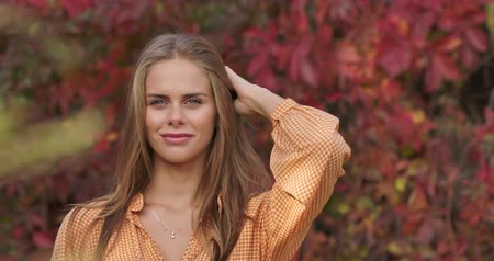 crows feet : Close-up of smiling girl standing on the background of red leaves and touching her brown hair. Charming confident woman in mustard dress posing at camera in autumn park. Cinema 4k footage ProRes HQ.