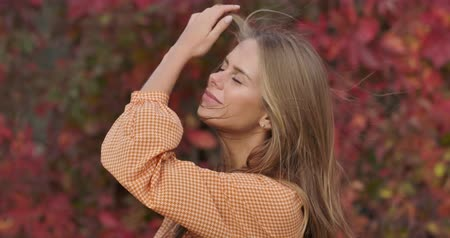 crows feet : Close-up of confident lady in mustard dress standing on the background of red leaves and holding her long hair in wind. Charming woman posing at camera in autumn park. Cinema 4k footage ProRes HQ.