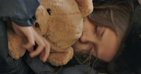 refugee crisis : Close-up face of a homeless girl with dirty face sleeping with the teddy bear. Exhausted child wearing hat with earflaps resting on the streets.