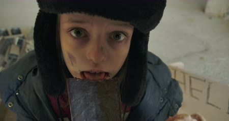 шок : Scared Caucasian homeless girl with dirty face and grey eyes greedily eating the chocolate bar. Little refugee in hat with earflaps having food to eat. Стоковые видеозаписи