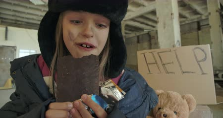 greedily : Portrait of a Caucasian homeless girl with dirty face and grey eyes greedily eating the chocolate bar. Excited child in hat with earflaps having food to eat. Stock Footage