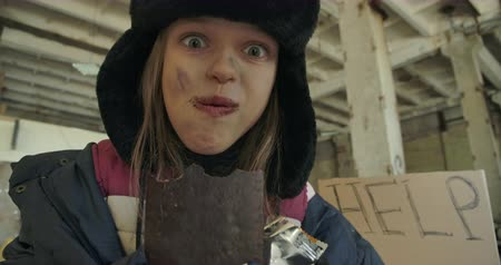 refugee crisis : Close-up portrait of a Caucasian homeless girl with dirty face and grey eyes greedily eating the chocolate bar. Excited child in hat with earflaps having food to eat. Stock Footage