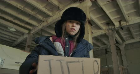 choque : Bottom view of a homeless Caucasian girl in dirty clothes raising the Help cardboard and looking at the camera. Hungry frozen child living on the streets. Stock Footage