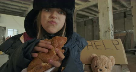 refugee crisis : Portrait of a Syrian refugee with dirty face and grey eyes greedily eating the bun. Homeless girl in hat with earflaps living on the streets. Stock Footage