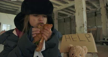 refugee crisis : Portrait of a Caucasian homeless girl with dirty face and grey eyes greedily eating the bun. Hungry child in hat with earflaps living on the streets.