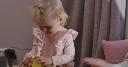 クラウン : Close-up of cute blond Caucasian child playing with toy crown at home. Pretty baby girl in pink blouse resting at home with mother. Happy childhood, leisure indoors. Cinema 4k footage ProRes HQ.