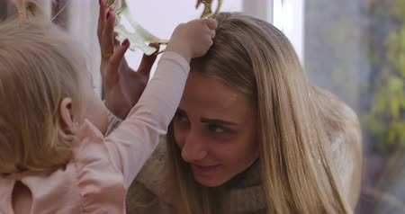 クラウン : Little Caucasian baby girl putting toy crown on mothers head. Back view of blond child playing with adult smiling woman at home. Happy parenthood, joy of maternity. Cinema 4k footage ProRes HQ.