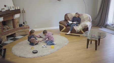 Long shot of three Caucasian children of different ages sitting at home in front of fireplace on weekends. Younger kids playing on soft carpet, elder sister sitting on couch and reading book. Stok Video