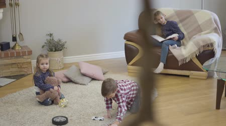 Shooting from stairs of playful Caucasian boy playing with toy car, his elder sister looking at siblings and smiling, and cute little girl looking at camera. Cheerful family resting on weekends.