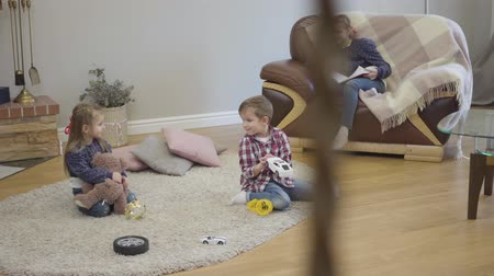 Three Caucasian children sitting at home and talking. Little girl and boy holding toys as their teenage sister siting on sofa with book. Kids resting indoors on weekends. Stok Video