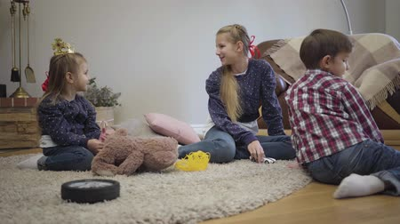 Portrait of Caucasian teenage girl playing with little brother and sister at home. Elder sister spending weekends with siblings indoors. Leisure, lifestyle, happiness.
