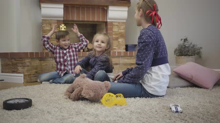 сестры : Portrait of cheerful Caucasian boy putting toy crown on head entertaining elder and younger sisters. Happy children having fun together indoors on weekends. Happiness, unity, resting.