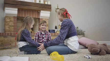 Happy Caucasian brother and two sisters sitting in front of fireplace and holding each others hands. Friendly siblings spending leisure time together at home. Unity, family, lifestyle. Stok Video
