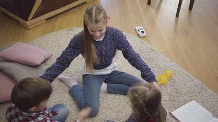 uç : Top view of cheerful Caucasian sisters and brother playing clapping hands. Smiling children having fun at home. Leisure, unity, childhood. Stok Video