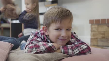 Portrait of little Caucasian brunette boy with nystagmus looking at camera and smiling as his sisters playing at the background. Unity, family, medicine and healthcare. Stok Video
