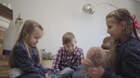 trzy : Side view of young Caucasian girl entertaining younger brother and sister at home. Little lady holding teddy bear and telling stories for siblings. Unity, happiness, leisure.