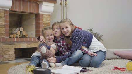 Camera approaching to cute Caucasian teenager hugging little boy and girl. Siblings looking at camera and smiling. Happy brother and sisters posing indoors.