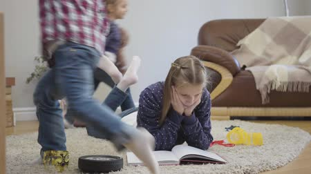 Portrait of cute Caucasian schoolgirl lying on soft carpet and reading as her younger siblings running around. Little brother and sister distracting girl from learning. Family, weekends, leisure.