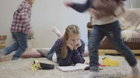 mókás : Two cheerful Caucasian children running around elder sister lying on soft carpet and reading. Teen girl trying to concentrate closing ears with fingers. Family, childhood.