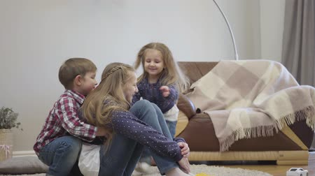 Little Caucasian girl and boy running to elder sister sitting on carpet and hugging her. Portrait of friendly siblings taking care of each other. Unity, support, family. Stok Video