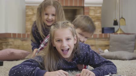 Close-up of smiling Caucasian girl lying on the floor as younger children scrawling on her. Cheerful brother and sisters having fun. Leisure, lifestyle, happiness.