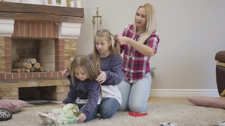 Camera approaching to happy Caucasian mother and two daughters spending weekends together. Woman braiding elder girls hair as she dealing with hairdress of younger sister. Happiness, unity, leisure. Stok Video