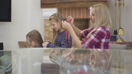 Side view of blond Caucasian mother and two daughters braiding each others hair. People reflecting in glass table standing at the foreground. Happiness, unity, leisure.
