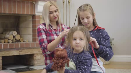 Camera approaching to pretty Caucasian girl playing with doll as her elder sister and mother braiding pigtails. Happy friendly family spending free time at home. Unity, leisure, lifestyle.