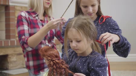 долл : Close-up portrait of cute Caucasian girl sitting with doll, elder sister and mother at the background. Female family members braiding pigtails indoors. Family, lifestyle, unity.