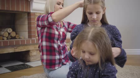Camera zooming out. Blond adult Caucasian woman doing hairdress for elder daughter, teenage girl braiding younger sister, little cute lady combing doll. Care, lifestyle, femininity.