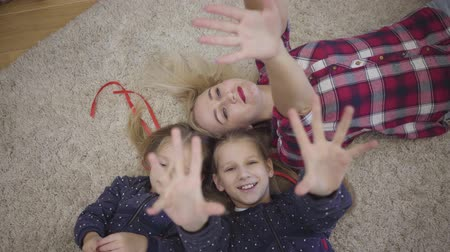 Camera approaching to young Caucasian mother lying with daughters on soft carpet holding hands up. Cheerful family resting at home on weekends. Happiness, unity, relaxation.