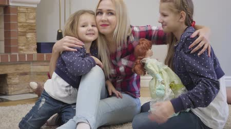 objetí : Portrait of happy Caucasian blond woman hugging and kissing daughters. Young mother taking care of her children indoors. Happiness, joy, leisure. Camera zooming in.