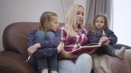 trzy : Portrait of pretty Caucasian woman sitting on couch with daughters and reading book. Mother educating children at home. Intelligence, family, unity.