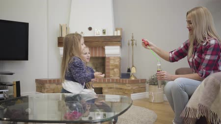bolha : Side view of cheerful Caucasian girl catching soap bubbles at home. Smiling blond woman blowing bubbles for daughters. Leisure, joy, unity. Stock Footage