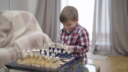 šachy : Portrait of smart Caucasian boy setting chess pieces on board. Little cute child starting playing with unrecognizable father. Intellect, intelligence.