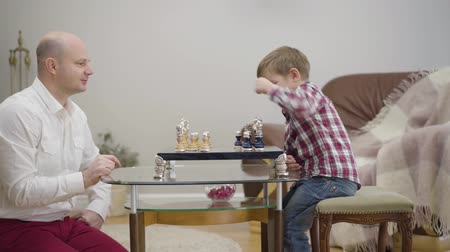 Side view of adult Caucasian man teaching little son to play chess. Little cute boy learning with father at home. Unity, intelligence, education. Stok Video