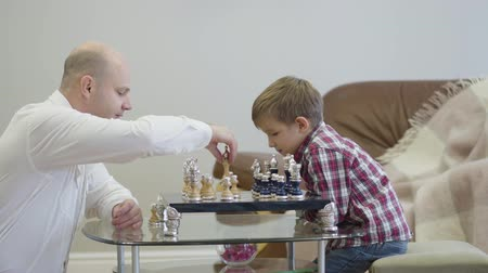 vista lateral : Side view of Caucasian man in white shirt sitting in front of chess board and playing with clever son. Cute smart boy spending free tine with father at home. Unity, intelligence, education.