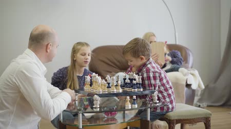 Young Caucasian father playing chess with son as elder daughter coming up. Mother and younger girl sitting on couch at the background and reading. Positive family spending weekends at home.