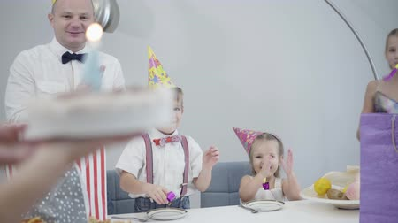 Camera following birthday cake to the table with family in party hats. Mother bringing pie with figure four and son blowing out candle. Happy friendly family celebrating together.