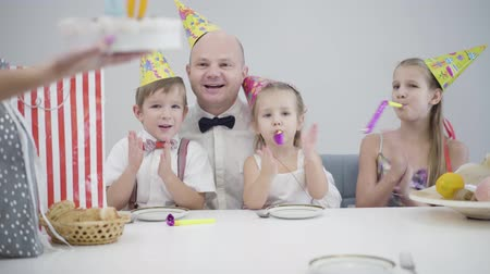 Female Caucasian hands bringing birthday cake with figure forty to the table, adult man blowing out candles, children kissing lovely father. Happy man celebrating with family at home.