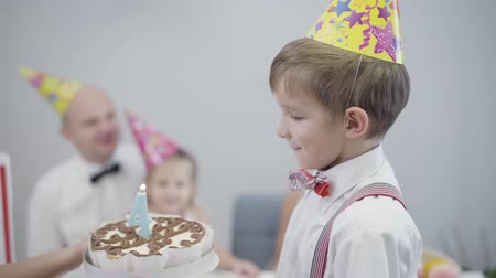 Side view close-up of Caucasian boy in party hat standing as female hands showing him birthday cake. Happy child celebrating birthday with family at home. Happiness, lifestyle. Stok Video
