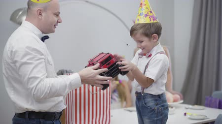 Camera approaching to cute little boy in party hat receiving toy car for his birthday. Happy child taking gift and hugging it. Celebration, birthday party, present.