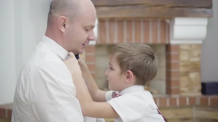 Close-up of cute Caucasian boy helping father to tie the bow tie. Diligent child supporting parent. Unity, fatherhood, happiness. Stok Video
