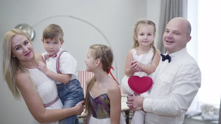 Portrait of big Caucasian family standing at home, talking, looking at camera and smiling. Happy people posing indoors. Man and woman holding children on hands as elder daughter standing between. Stok Video