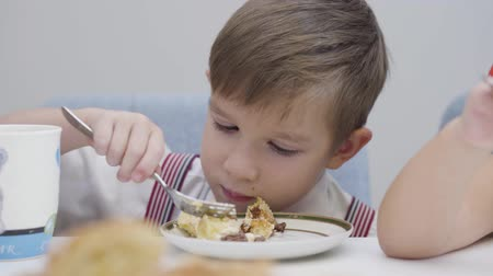 Close-up face of little Caucasian boy eating tasty cake. Cute child sitting at the table and enjoying sweet food. Happiness, leisure, lifestyle.