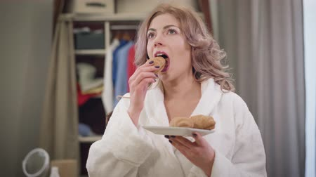 Portrait of beautiful Caucasian woman in white bathrobe smelling tasty croissant and biting it. Charming lady enjoying sweet food at home in the morning. Diet, beauty, lifestyle.