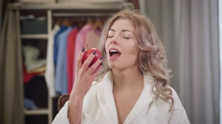 Portrait of charming Caucasian girl biting red apple and showing thumb up. Beautiful young woman eating healthy food at home. Nutrition, diet, lifestyle.