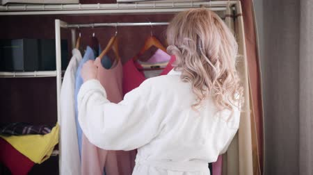 Back view of young Caucasian woman in white bathrobe choosing outfit in wardrobe. Girl shifting hangers with clothes in the morning at home. Fashion, lifestyle.