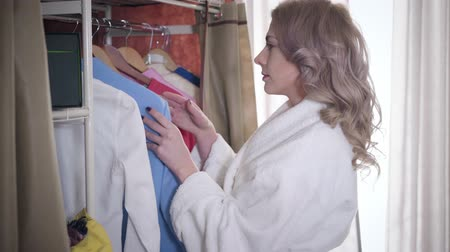 seçme : Side view of beautiful Caucasian girl choosing clothes in the morning. Confident young woman standing in front of wardrobe with different outfit. Lifestyle, fashion, style.